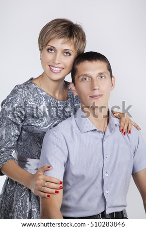 Portrait adult married couple on white background in studio. Looking at camera wife smiling hugging a husband