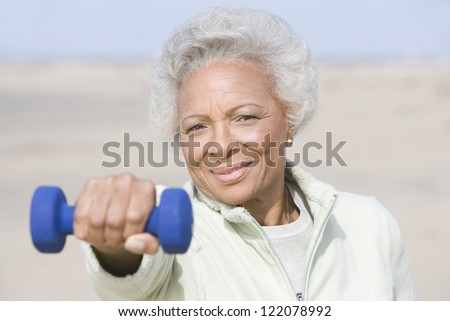 Portrait an African American senior woman exercising with dumbbells at beach