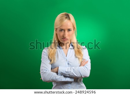 portrait angry blonde woman on green background - stock photo
