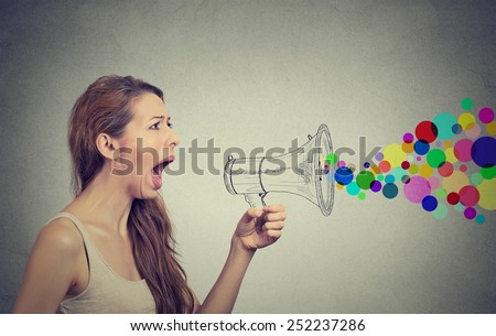 Portrait angry screaming young woman holding megaphone isolated on grey wall background. Negative face expression emotion feelings. Propaganda, breaking news, power, social media communication concept - stock photo