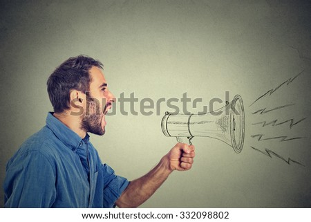 Portrait angry young man holding screaming in megaphone isolated on grey wall background. Negative face expression emotion feeling. Propaganda, breaking news, power, social media communication concept - stock photo
