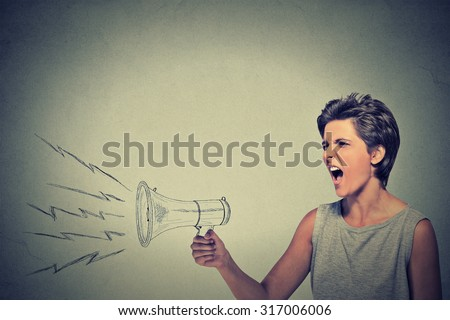 Portrait angry young woman holding screaming in megaphone isolated grey wall background. Negative face expression emotion feelings. Propaganda, breaking news, power, social media communication concept - stock photo
