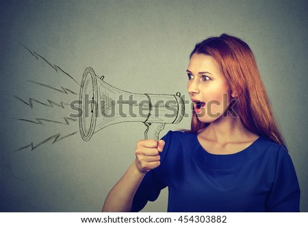 Portrait angry young woman screaming in megaphone isolated on grey wall background. Negative face expression emotion feelings. Propaganda, breaking news, power, social media communication concept - stock photo