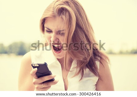 Portrait angry young woman screaming on mobile phone standing outside with city background. Negative emotions feelings  - stock photo