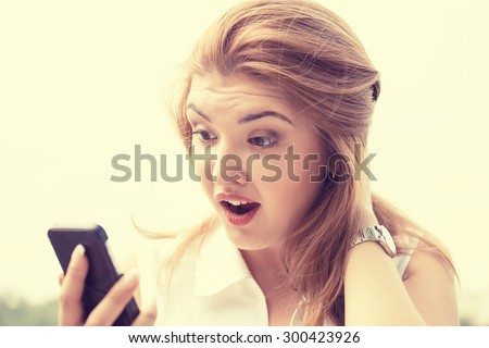 portrait anxious young girl woman looking at phone reading seeing bad news or photos with disgusting emotion on her face isolated outside outdoors background. Human emotion, reaction, expression - stock photo