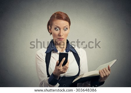 Portrait anxious young woman holding book looking at phone seeing bad news or photos with disgusting emotion on her face isolated on gray wall background. Human emotion, reaction, expression - stock photo