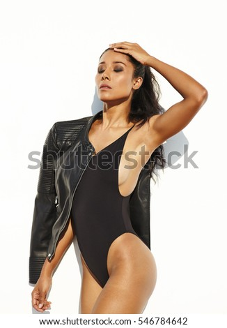Portrait asian model wwith long black hair, in the body and black leather jacket opposite white background