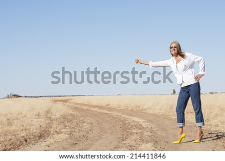 Portrait attractive and confident attractive mature woman in high heels, hitchhiking in rural country , smiling, happy, thumb up, with horizon and blue sky as background and copy space.