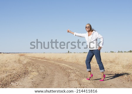 Portrait attractive and confident attractive mature woman in pink high heel shoes, traveling, hitchhiking in rural country, smiling, thumb up, with horizon and blue sky as background and copy space.