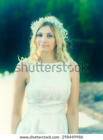 Portrait, attractive blond woman wearing a flower head wreath, summer day, cross processed image - stock photo