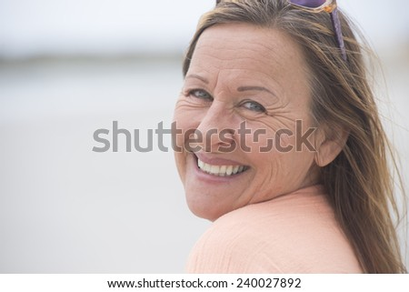 Portrait attractive mature woman happy confident outdoor, peaceful and relaxed and smiling pose, blurred background and copy space. - stock photo