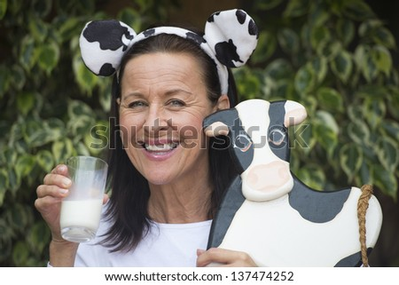 Portrait attractive mature woman happy relaxed friendly with glass of milk in hand downy beard or milksop, funny cow ears on head and wooden cow in arm outdoor with blurred background. - stock photo