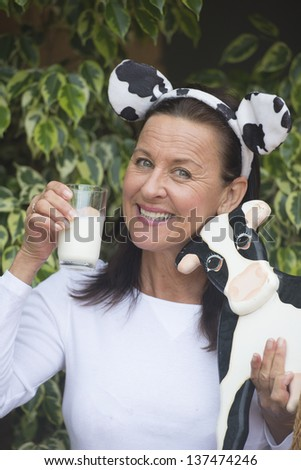 Portrait attractive mature woman happy relaxed friendly with glass of milk in hand, funny cow ears on head and wooden cow in arm outdoor with blurred background. - stock photo