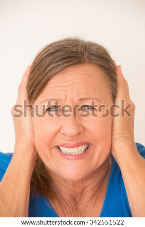 Portrait attractive mature woman in pain with migraine headache, covering ears with hands, isolated, bright background.