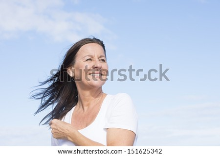 Portrait attractive mature woman joyful and happy retired, keeping healthy and fit, isolated on blue sky background and with copy space. - stock photo