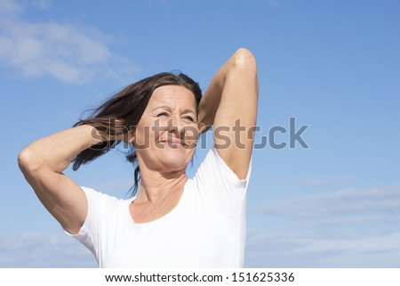 Portrait attractive mature woman joyful and happy retired, keeping healthy and fit, with arms up, isolated on blue sky background and with copy space. - stock photo