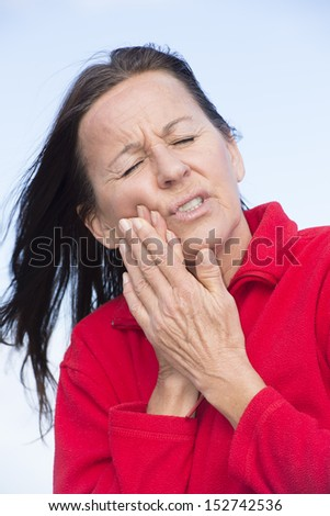 Portrait attractive mature woman outdoor in stress and pain, dental problems, suffering from toothache, pressing hands on chin. - stock photo