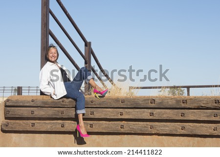 Portrait attractive mature woman posing relaxed sitting at metal fence in rural country area, wearing pink high heel shoes, with blue sky as background and copy space.