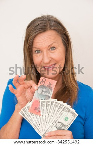 Portrait attractive mature woman presenting relaxed smiling Australian and  US dollar notes, isolated, bright background.