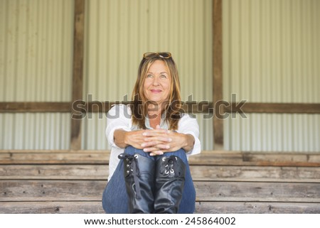Portrait attractive mature woman sitting confident outdoor on bench relaxed and happy looking, watching, observing and waiting. - stock photo