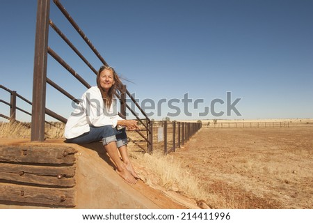 Portrait attractive mature woman sitting relaxed smiling at metal fence line in rural farming area in outback Australia, with dry arid agricultural country and blue sky as background and copy space. - stock photo