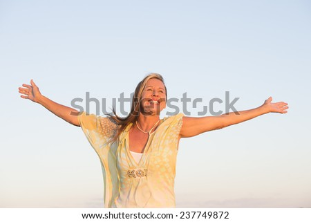 Portrait attractive mature woman, smiling joyful, successful, confident and happy with arms up, clear sky as outdoor background and copy space. - stock photo