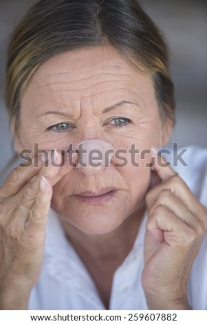 Portrait attractive mature woman stressed in pain with band aid on nose and unhappy facial expression, blurred background.