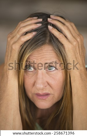 Portrait attractive mature woman, stressed, scared, unhappy frightened look, hands covering head, blurred background. - stock photo