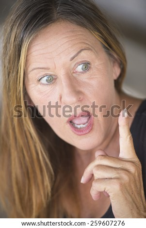 Portrait attractive mature woman, surprised, shocked, interested facial expression, with point finger, blurred background. - stock photo