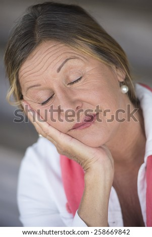 Portrait attractive mature woman tired, closed eyes, worn out, thoughtful, serene with chin resting on hand, blurred background. - stock photo