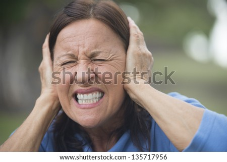 Portrait attractive mature woman with closed eyes covering frustrated, angry or in anxiety her ears with hands, upset shocked, isolated with blurred outdoor background. - stock photo