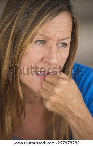 Portrait attractive mature woman with nervous insecure stressed facial expression, biting finger nails, blurred background. - stock photo