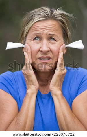Portrait attractive mature woman with stressed facial expression, with tissues in ears for noise protection, outdoor blurred background. - stock photo