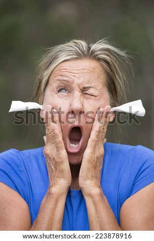 Portrait attractive mature woman with stressed shocked facial expression, with tissues as earplugs for noise protection, outdoor blurred background. - stock photo