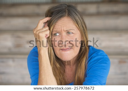Portrait attractive mature woman with upset thoughtful angry facial expression, lonely worried, blurred background. - stock photo