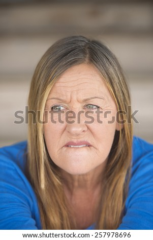 Portrait attractive mature woman with worried nervous thoughtful angry expression, , blurred background. - stock photo