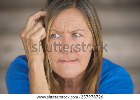 Portrait attractive mature woman with worried thoughtful angry expression, lonely and nervous, blurred background. - stock photo