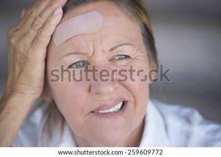 Portrait attractive stressed mature woman , suffering painful headache, with band aid on injured forehead, blurred background. - stock photo
