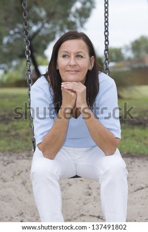 Portrait attractive thoughtful mature woman sitting relaxed and happy on swing at playground in park outdoor, with confident face and blurred background - stock photo