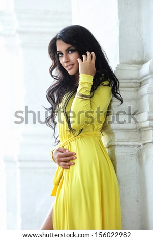 Portrait attractive young woman in yellow dress - stock photo
