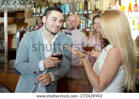 Portrait bar visitors waiting for table and drinking wine at tavern. Focus on the man - stock photo