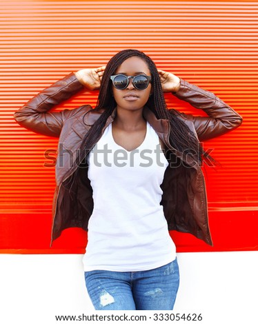 Portrait beautiful african woman wearing a leather jacket and sunglasses in city over red background - stock photo