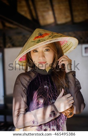 Portrait Beautiful Asian girl with Vietnamese dress (Ao dai) and Old House in farm