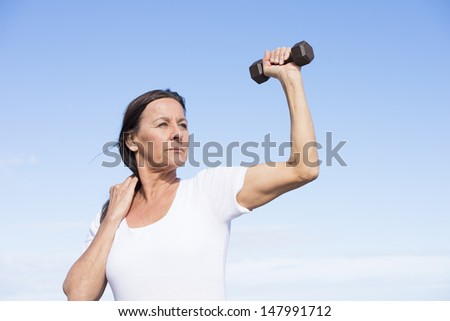 Portrait beautiful confident mature woman exercising with weights, keeping healthy and fit, focused view, determined, positive, successful, with blue sky as background and copy space. - stock photo