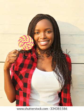 Portrait beautiful happy smiling african woman with sweet lollipop, wearing a red checkered shirt in city - stock photo