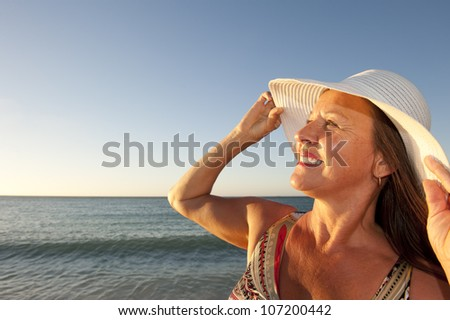 Portrait beautiful mature woman at sunset beach, wearing white wide rimmed hat, friendly and happy, isolated with ocean and blue sky as background and copy space. - stock photo