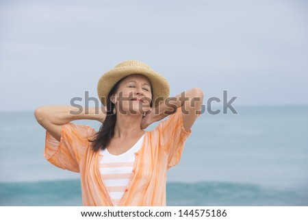 Portrait beautiful mature woman standing relaxed and friendly smiling at beach, wearing orange blouse and hat, with ocean and horizon as blurred background and copy space. - stock photo