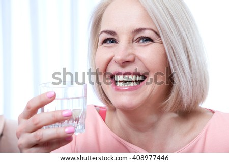 Portrait beautiful middle aged woman drinking water in the morning. Woman's face close up  - stock photo