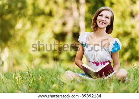 portrait beautiful short-haired young woman reading book sat grass smiling background summer meadow trees green grass
