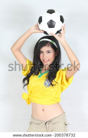 Portrait Beautiful woman hold ball over her head with wearing Brazil football top - stock photo